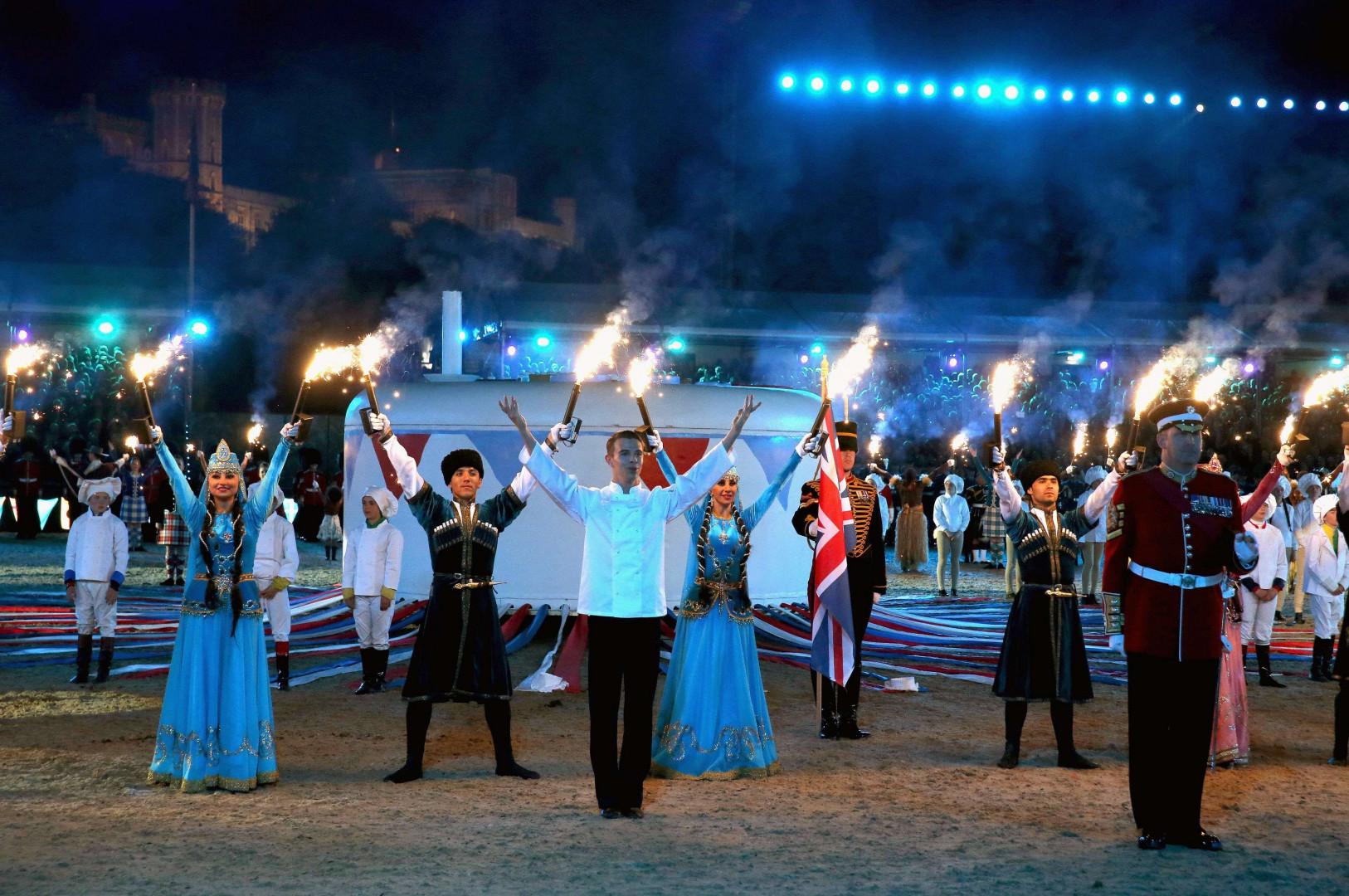 Les artistes lèvent leurs torches devant le gâteau d'anniversaire géant en l'honneur d'Elizabeth II