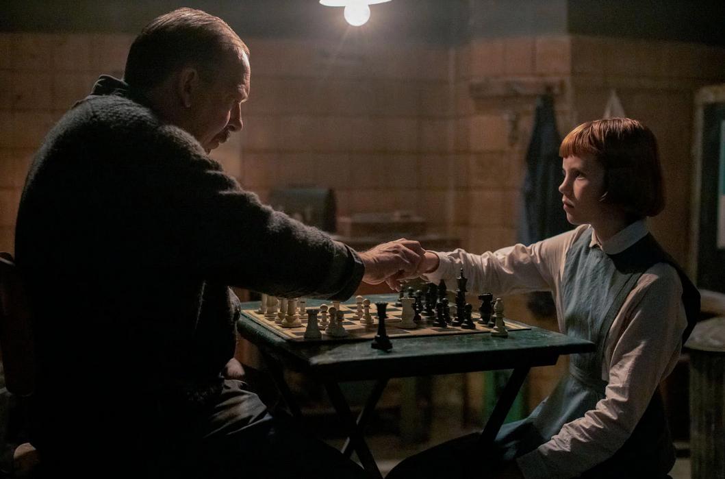Bill Camp incarne Monsieur Shaibel qui apprend à la jeune Beth (Isla Johnsto) les échecs