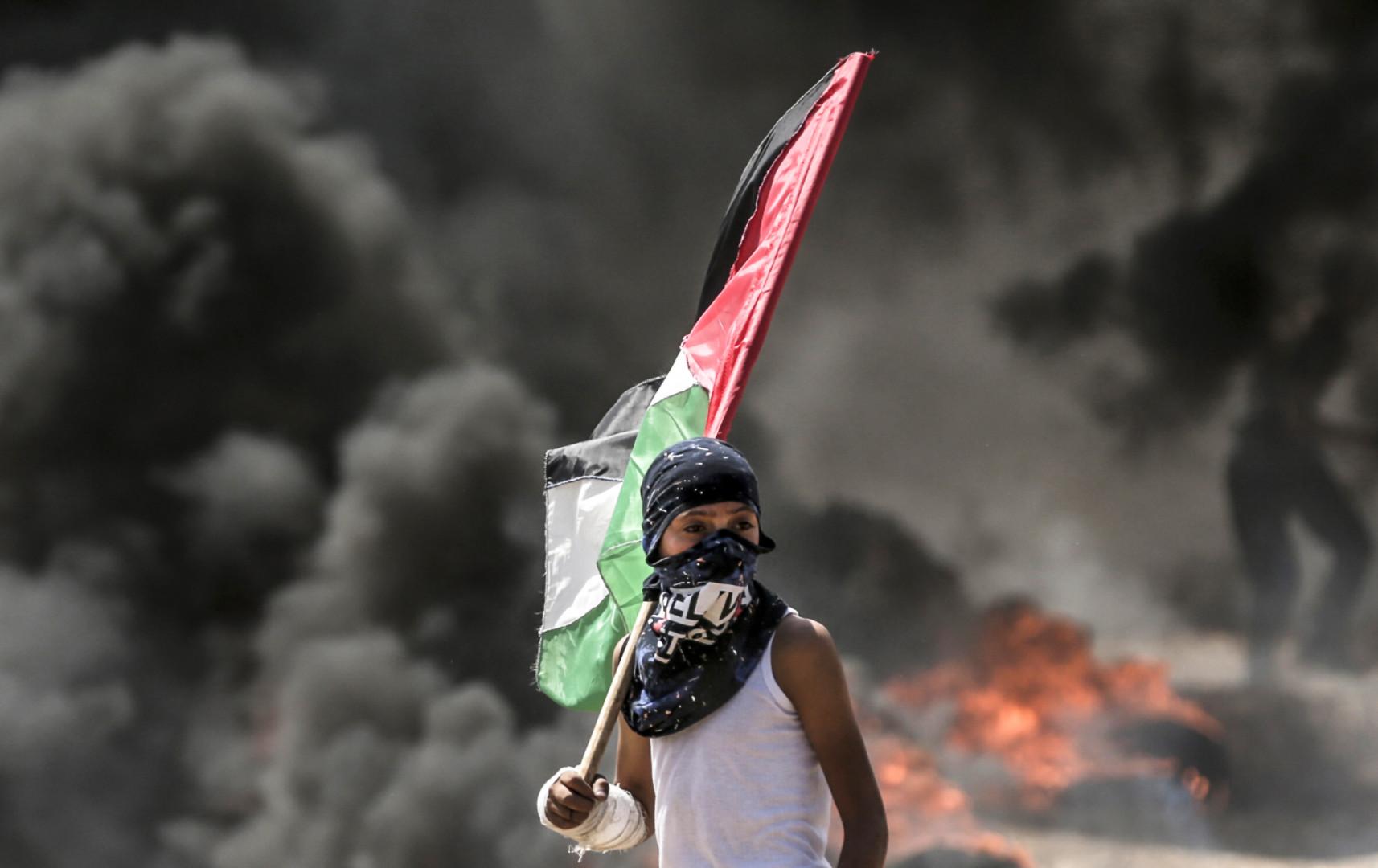 Un enfant palestinien arbore un drapeau national lors de la manifestation contre le transfert de l'ambassade américaine à Jérusalem lundi 14 mai
