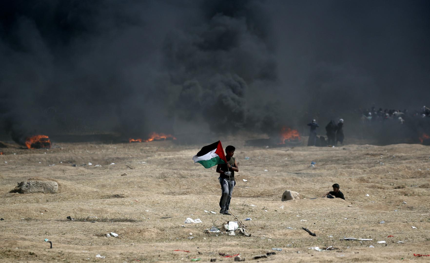 Un homme porte un drapeau palestinien pendant les heurts entre l'armée israélienne et les manifestants gazaouis lundi 14 mai