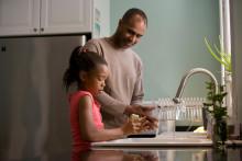 Un père et sa fille dans leur cuisine. (Illustration)