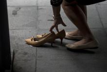 Une employée change de chaussures en sortant de son travail à Manille, aux Philippines