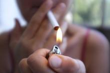 Une femme fume une cigarette (illustration)