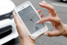 Une femme commande un Uber sur son smartphone (illustration)