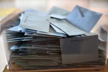 Des bulletins de vote dans une urne.