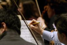 Un musicien de l'Orchestre National de France annote sa partition lors d'une répétition au théâtre des Champs Elysées, le 18 février 2004 à Paris.