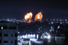 Des explosions illuminent le ciel nocturne au-dessus de bâtiments dans la ville de Gaza alors que les forces israéliennes bombardent l'enclave palestinienne, le 16 juin 2021.