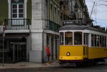 Une femme se tient à côté d'un tramway dans le centre-ville de Lisbonne, au Portugal, le 18 juin 2021. Pour lutter contre l'épidemie, le pays instaure de nouveau un couvre-feu nocturne à partir du vendredi 2 juillet.