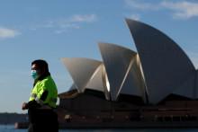Un homme portant un masque passe devant l'Opéra de Sydney, en Australie, le 13 juillet 2021. (Illustration)