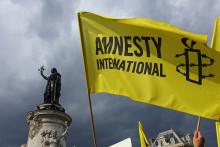 Des manifestants agitent le drapeau d'Amnesty International lors d'une manifestation de solidarité avec les migrants sur la place de la République à Paris, le 5 septembre 2015. (Illustration)