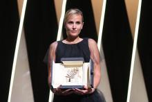 """Julia Ducournau avec la Palme d'Or dans les mains pour son film """"Titane"""", sur la scène du festival de Cannes le 17 juillet 2021."""