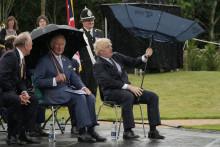 Le Premier ministre britannique Boris Johnson tentant d'ouvrir son parapluie à côté du prince Charles, au National Memorial Arboretum à Alrewas, le juillet 28, 2021