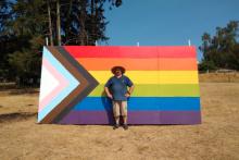 JaybillMcCarthy pose devant son drapeau LGBT+ géant, peint sur du bois et installé dans son jardin.