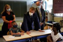 Le président Emmanuel Macron s'entretient avec des enfants lors de sa visite à l'école primaire de Bouge pour la rentrée scolaire le 2 septembre 2021.