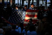 Des pompiers et des policiers tiennent le drapeau américain, à New York le 11 septembre 2021