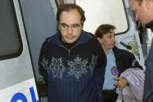 Denis Waxin sort d'un fourgon cellulaire escorté par des policiers, le 29 mai 2002 au tribunal de Douai