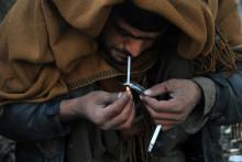 Un Afghan en train de fumer de l'héroïne en 2014 à Jalalabad