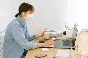 Une femme portant son masque chez elle en télétravail (Image d'illustration).