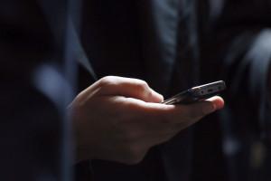 Un homme tenant son téléphone portable (illustration).