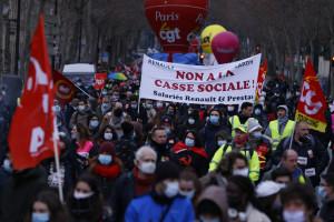 """Des manifestants défilent avec une banderole en français """"Dites non à la rupture sociale"""" lors d'un rassemblement contre les plans sociaux à Paris, le 23 janvier 2021."""