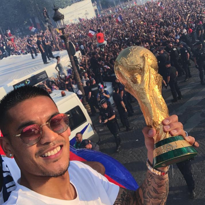 Alphonse Areola, son téléphone dans une main, la Coupe du Monde dans l'autre, le temps d'un selfie sur les Champs-Élysées lundi 16 juillet 2018