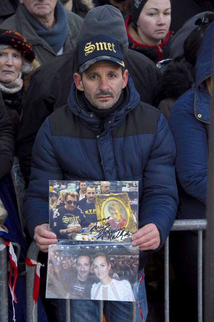 Très dignes, de nombreux fans, à l'image de cet homme, ont manifesté leur peine en montrant des souvenirs de concerts.