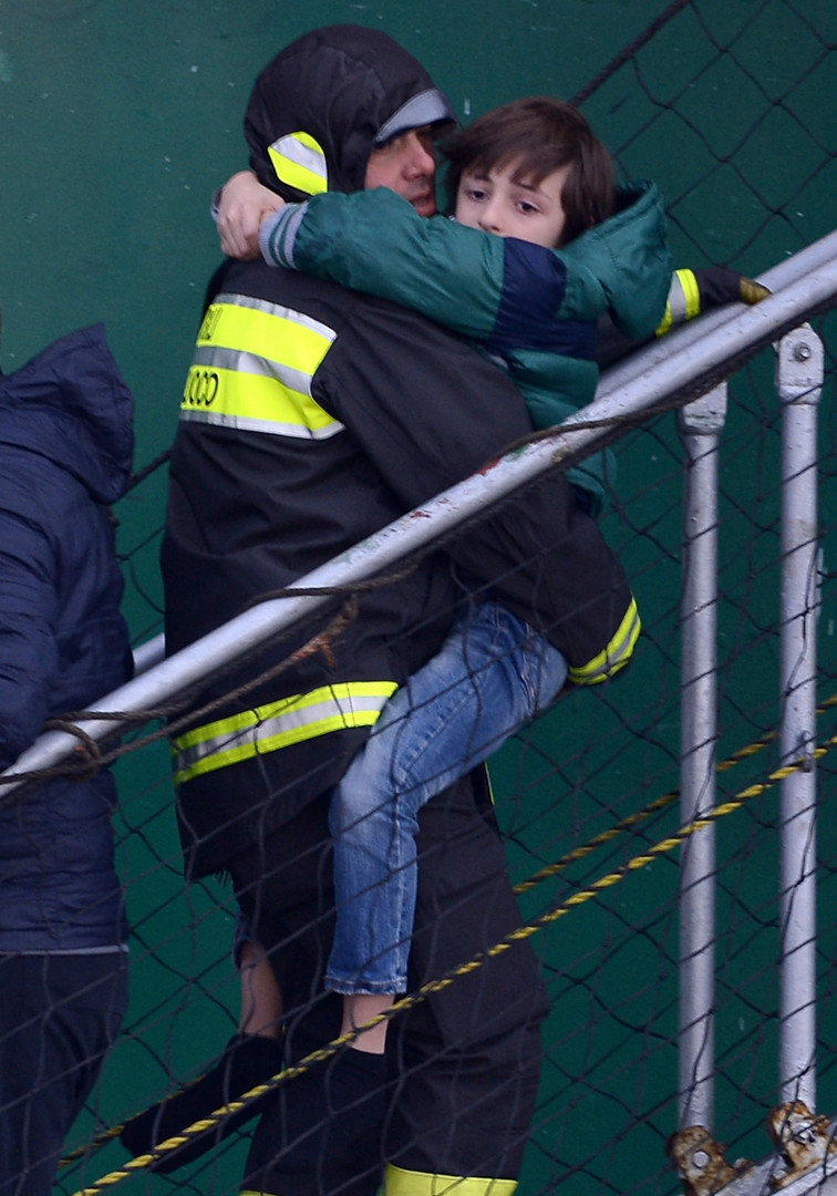 Un secouriste fait descendre un garçon du paquebot de sauvetage
