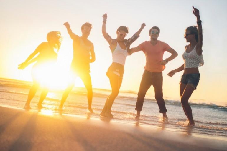 Un coucher de soleil avec des jeunes sur une plage (illustration)