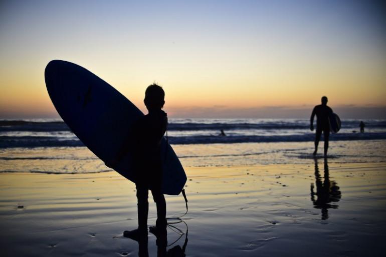 Un petit surfeur sur la plage au Chili (Illustration)