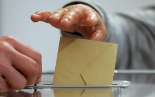 Un électeur glisse une bulletin de vote dans une urne, en France.