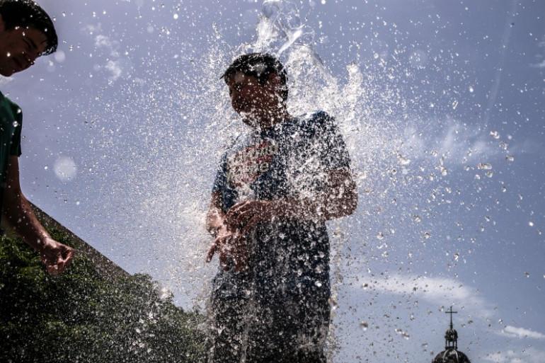 Un enfant joue dans une fontaine à Lyon, le 9 juin 2014.