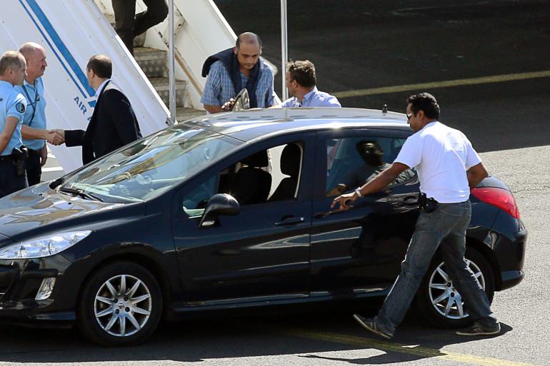 Le juge Hakim Karki (pull sur les épaules) arrive à l'aéroport de Sainte-Marie de La Réunion le 7 juillet 2014 sous escorte policière.