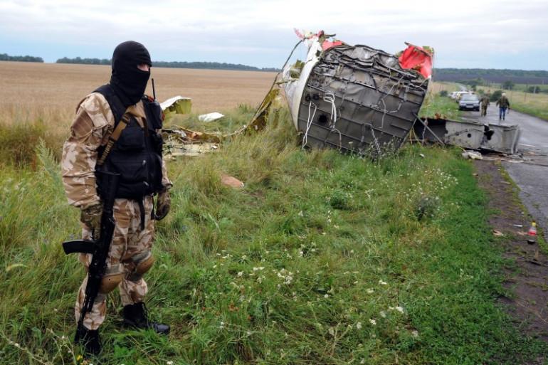 Un militant pro-russe, armé et cagoulé, garde des débris de l'avion de la Malaysia Airlines, le 18 juillet 2014 à Grabove