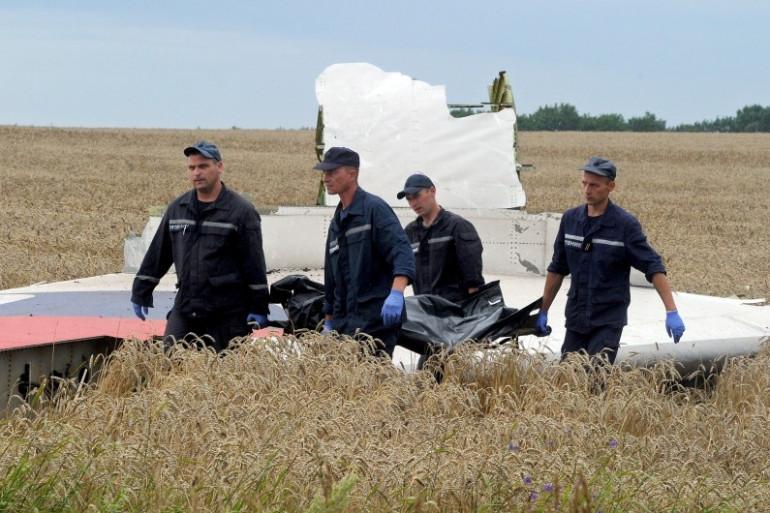 Des secouristes ukrainiens évacuent un corps devant un débris de la carlingue de l'avion, le 19 juillet 2014 en Ukraine