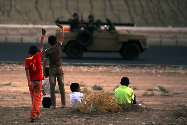 Des enfants Yazidis saluent le passage de combattants peshmergas au Kurdistan irakien