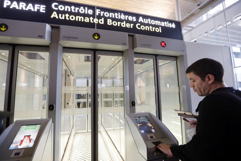 Un homme passe devant au contrôle automatique des passeports à l'aéroport de Roissy