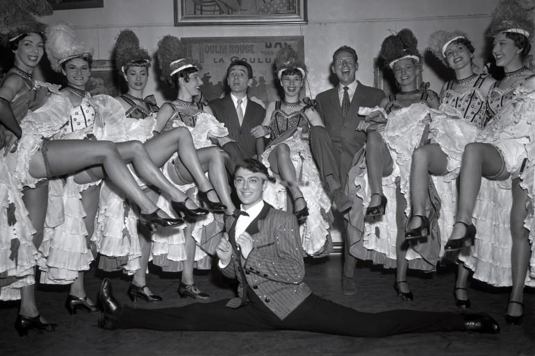 Le chanteur français Charles Trenet danse le French Cancan avec Charles Aznavour au Moulin Rouge en 1955