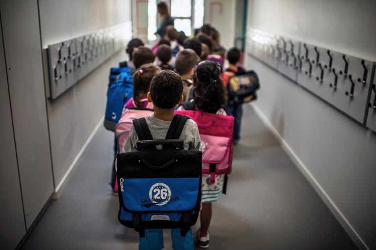Des enfants s'apprêtent à entrer dans leur salle de classe, le 3 septembre 2014, jour de rentrée, à Lyon (archives)