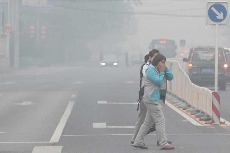 Deux habitantes se protègent de la pollution à Pékin, le 8 octobre 2014.