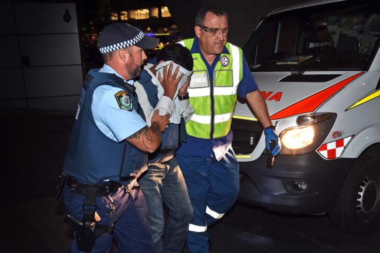Sydney : un otage est escorté par un policier et un médecin, le 15 décembre 2014