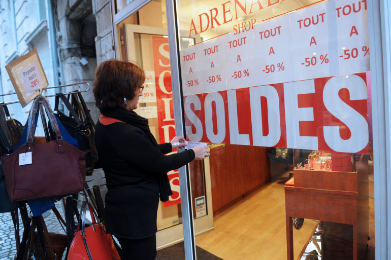 Une commerçant installe une affiche pour les soldes dans sa vitrine.