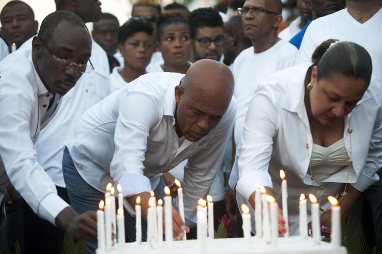 Le président haïtien Michel Martelly (au centre) entourée de la Première dame Sophia Martelly et du Premier ministre Evans Paul rendent hommage aux victimes de l'accident du carnaval de Port-au-Prince, le 17 février 2015.