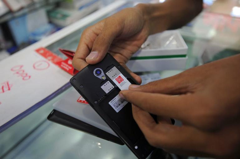 Un vendeur introduit une carte SIM dans un téléphone (illustration).
