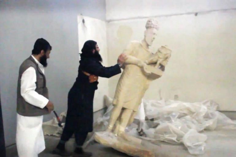 Un jihadiste de l'Etat islamique en train de détruire une sculpture à Mossoul, en Irak.