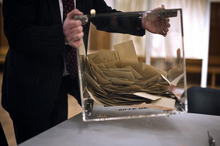 Un scrutateur vide l'urne contenant les bulletins de vote, le 20 mars 2011 dans un bureau de vote de Dijon, lors du dépouillement des votes du premier tour des élections cantonales