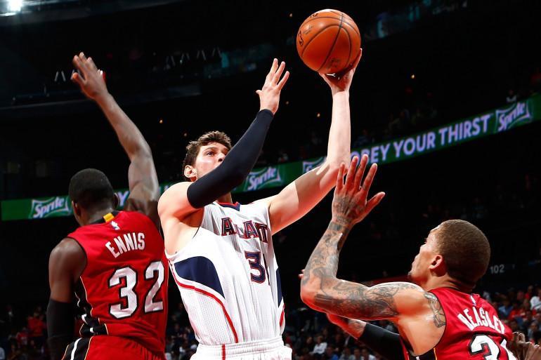 Mike Muscala #31 des Atlanta Hawks contre James Ennis #32 et Michael Beasley #30 des Miami Heat à Atlanta le 27 mars 2015.