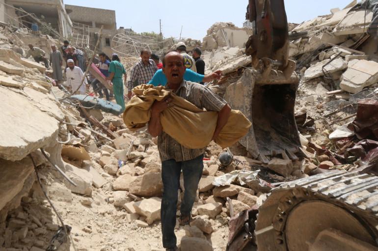 Un Syrien porte un corps après un bombardement à Alep