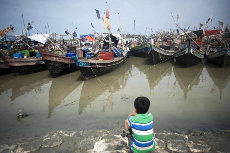 Un petit garçon de l'ethnie des Rohingyas, une minorité musulmane persécutée en Birmanie, regarde les bateaux dans un port de l'État d'Arakan, sur la côte nord-ouest du pays le 22 mai 2015.