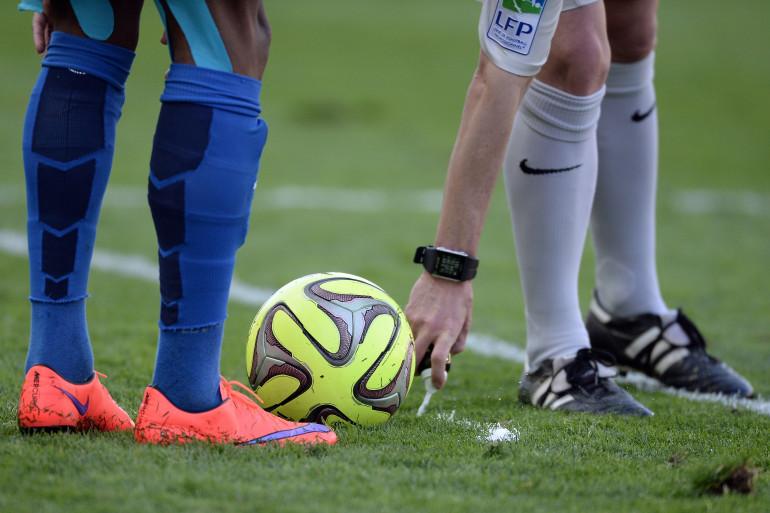 Football : un arbitre place le ballon sur le terrain (illustration).