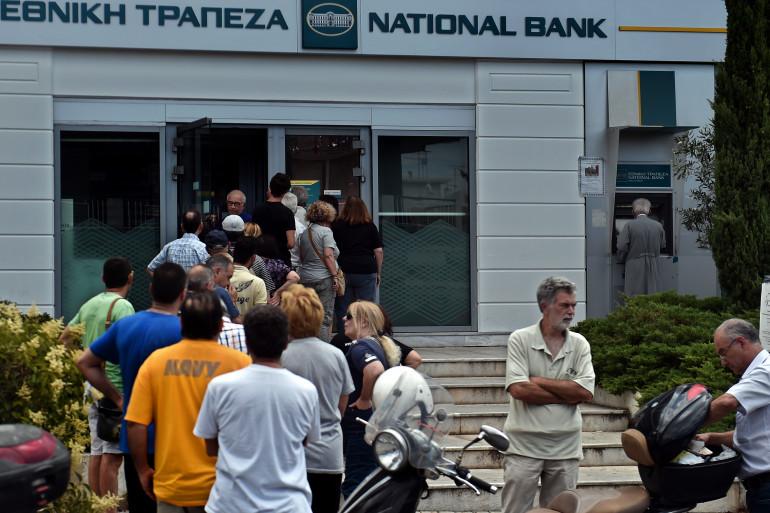 Des gens font la queue pour retirer de l'argent de la Banque nationale de la Grèce